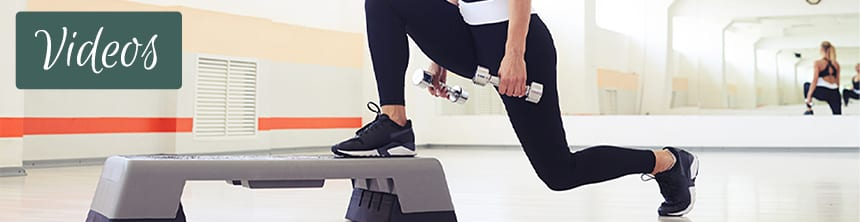 Mid Shot Of Woman Exercising Step Aerobics With Dumbbells